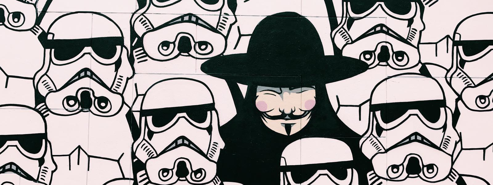 Ein Mann verkleidet als Guy Fawkes umgeben von Stormtrooper aus dem Star Wars Universum