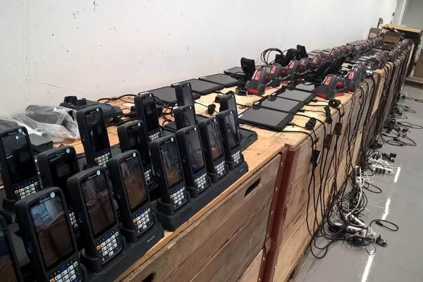 Mehrere Handscanner und Tablets auf Kästen im Lager