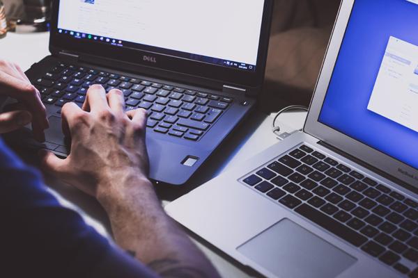 Ein Mann bedient ein Windows-Laptop und ein Macbook