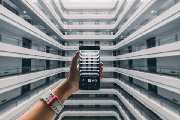 Eine Frau fotografiert den Innenhof eines Wohnkomplexes