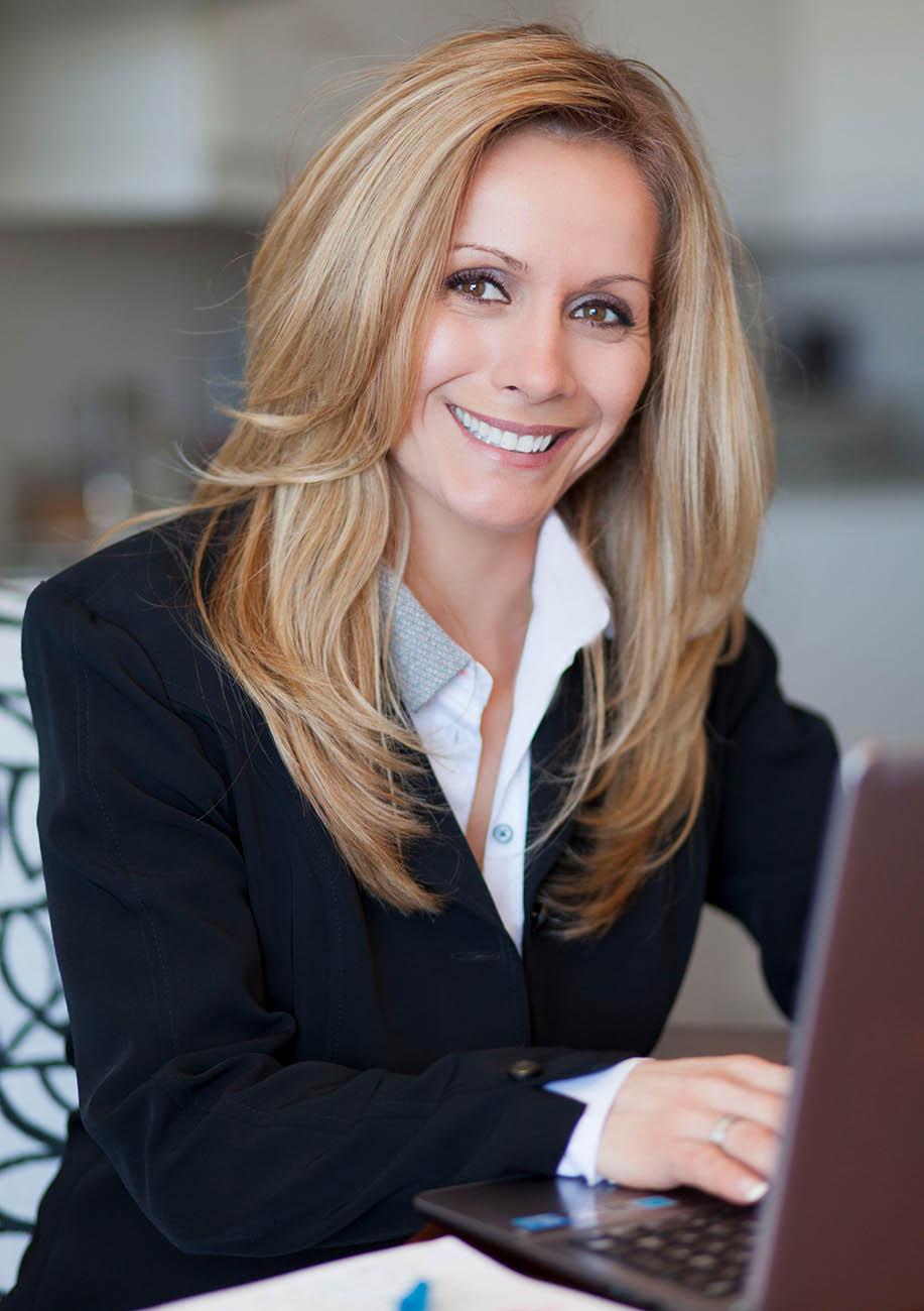 Frau Janina Jones arbeitet am Laptop und lächelt