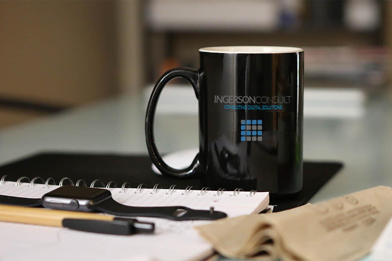 Eine schwarze Tasse steht auf einem Arbeitsplatz zusammen mit einem Notizbuch und Apple Watch