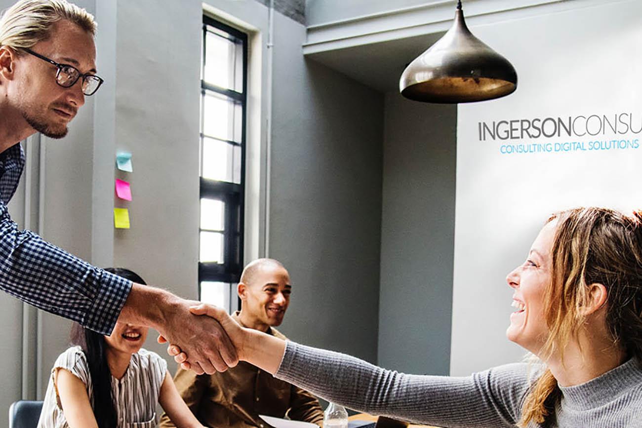 Ein Mann gibt seiner Arbeitskollegin die Hand im Meeting