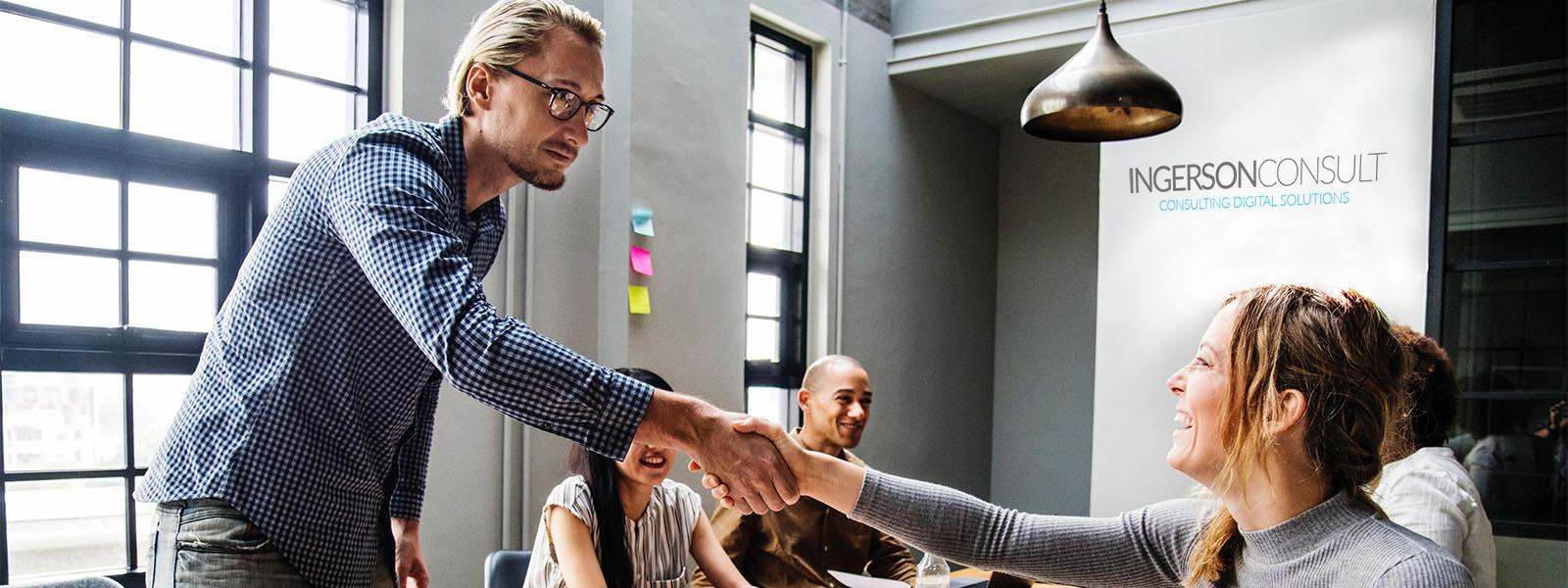 Junger Mann begrüßt seine Kollegen im Besprechungsraum