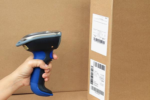 Logistikfachkraft scannt im Versandlager Produkte ein.